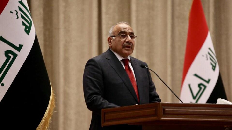 Adel Abdel Mahdi parle sur un podium, entouré de deux drapeaux irakiens.