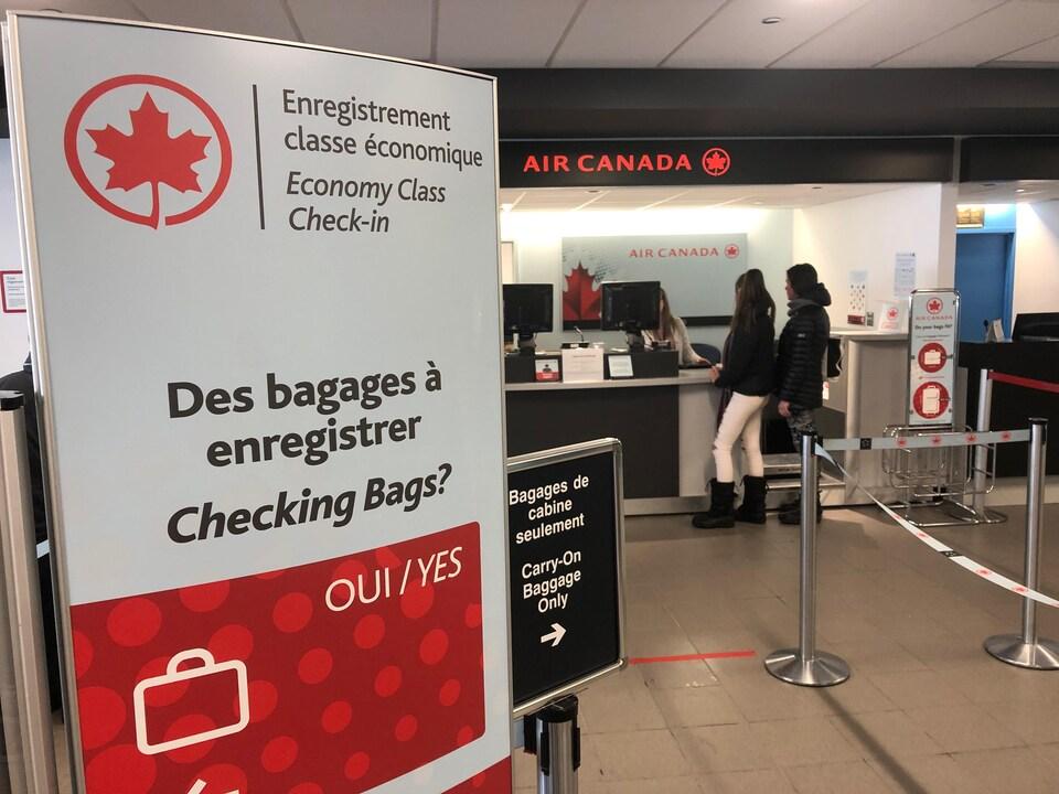 On voit un comptoir dans un aéroport au dessus duquel on peut lire Air Canada.