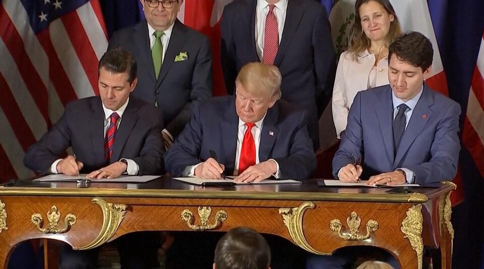 Enrique Pena Nieto, Donald Trump et Justin Trudeau signent une copie de l'accord sur une table en bois ornementée.