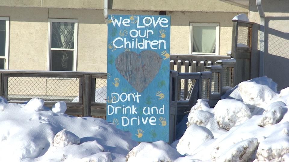 Une affiche bleue plantée dans la neige.