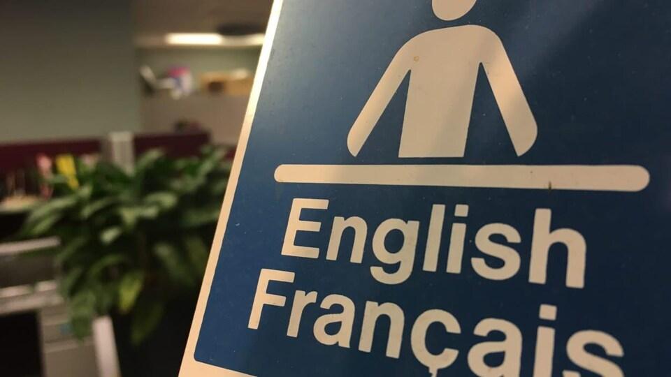 Une affiche où s'est écrit English français avec une icône d'un homme devant un bureau.