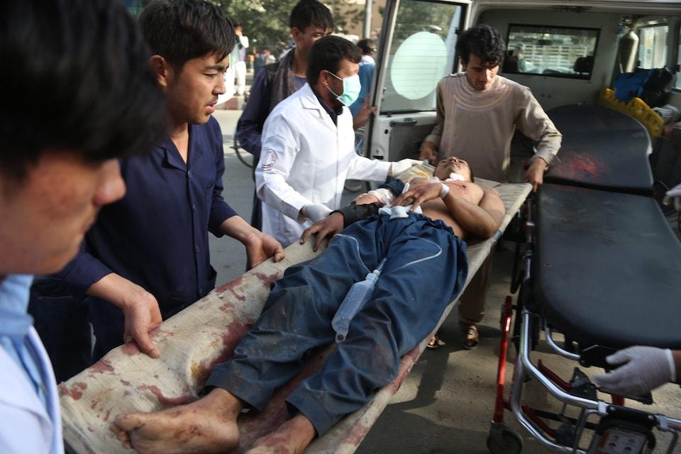 Un homme, torse nu, est transporté sur une civière par plusieurs hommes. La civière est ensanglantée.