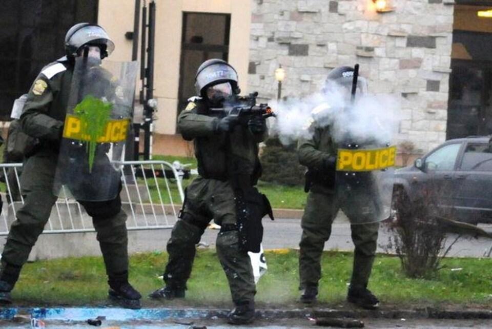 L'agent Burelle au milieu de ses collègues utilise son arme d'impact