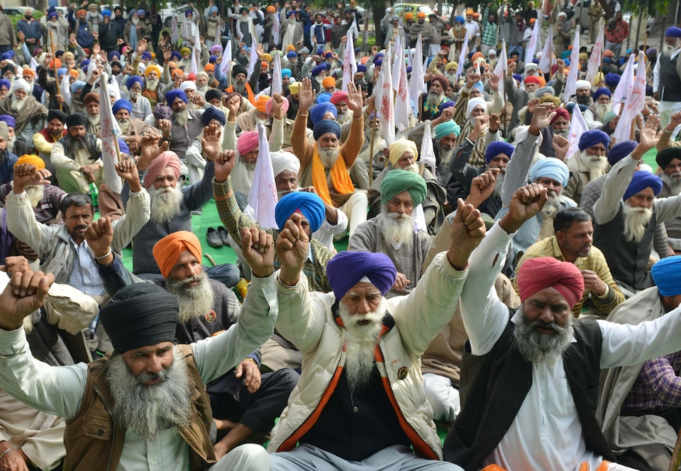 Des hommes âgés portant le turban et la barbe, assis par terre, lèvent leurs poings.