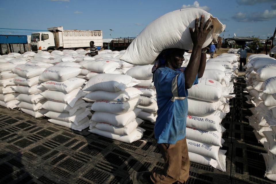 Un homme transporte sur sa tête un gros sac de nourriture, et en arrière-plan, des piles de sac.
