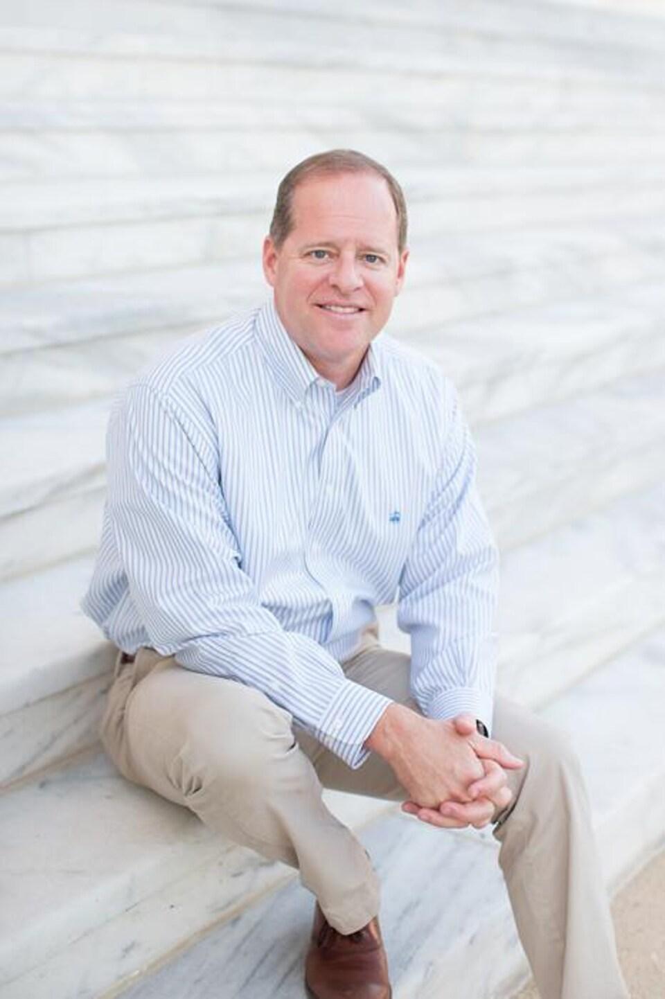Un homme souriant, en chemise et pantalons de ville, est assis dans un escalier. Il regarde la caméra.