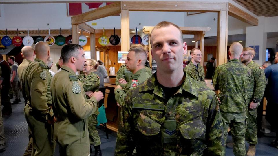 Un militaire regarde la caméra devant plusieurs militaires.