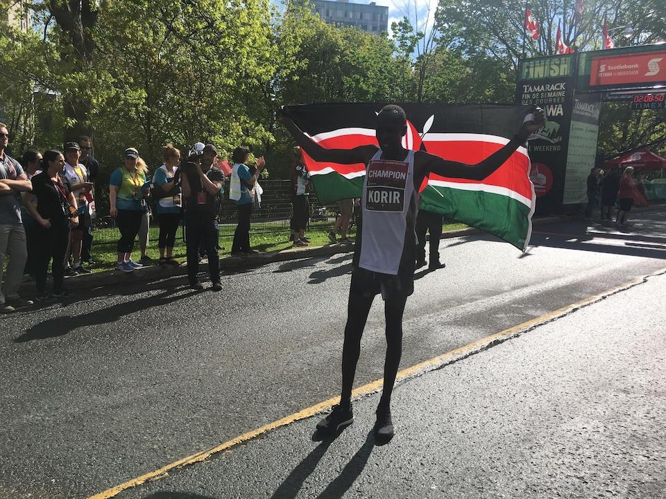 Un marathonien avec un drapeau du Kenya.