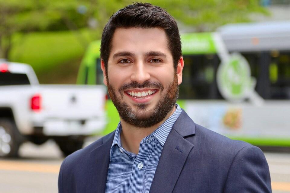 Le porte-parole du ministère des Transports, Alexandre Bougie, pose devant des véhicules.