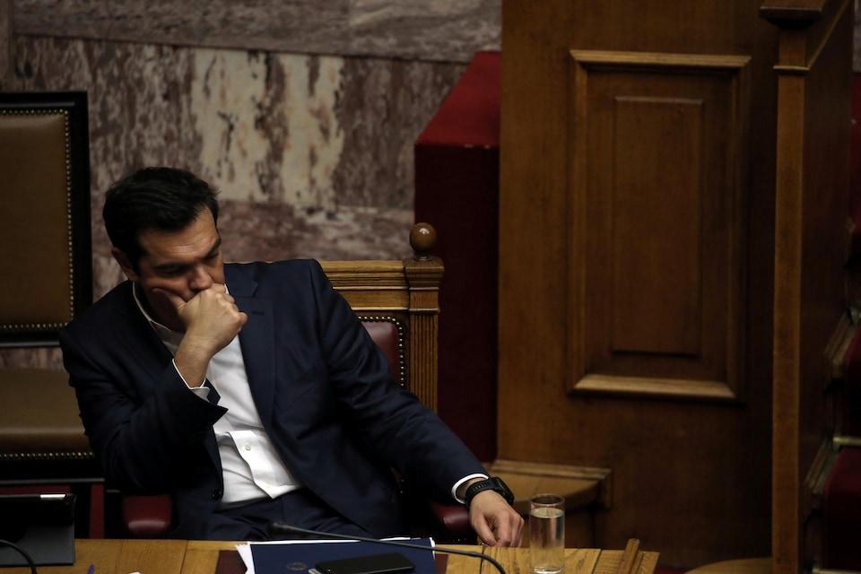 Le premier ministre grec Alexis Tsipras, assis sur une chaise en bois, ayant l'air perdu dans ses pensées.