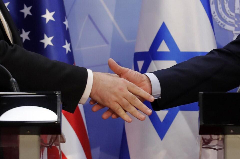 Poignée de mains devant des drapeaux américain et israélien.