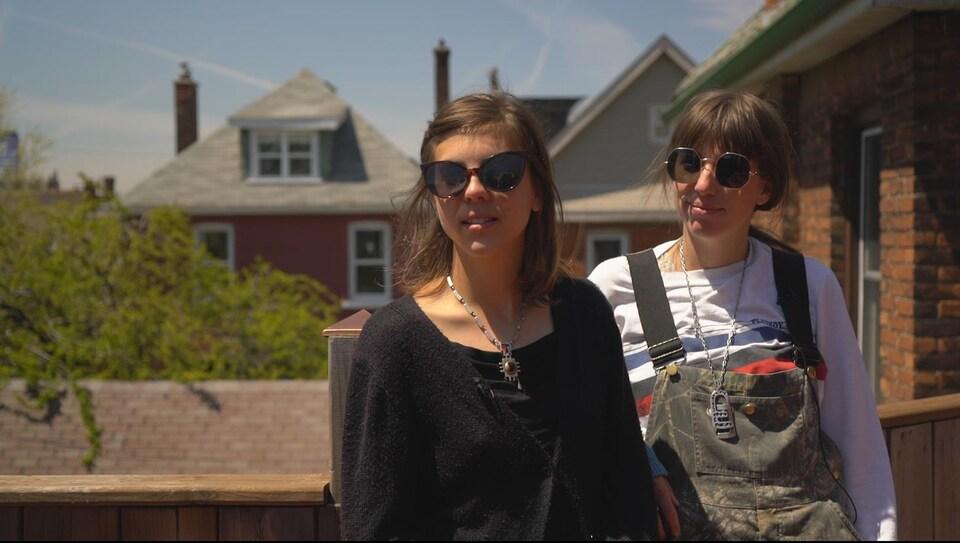 Deux jeunes femmes debout sur un balcon derrière une maison au soleil