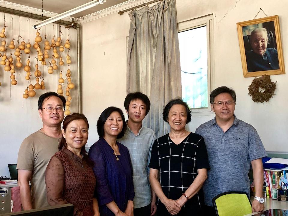 La directrice Luo Zhaohong, entourée du personnel de l'école Nongjianv, sous le portrait de l'écrivaine Bing Xin. Pékin, septembre 2018.