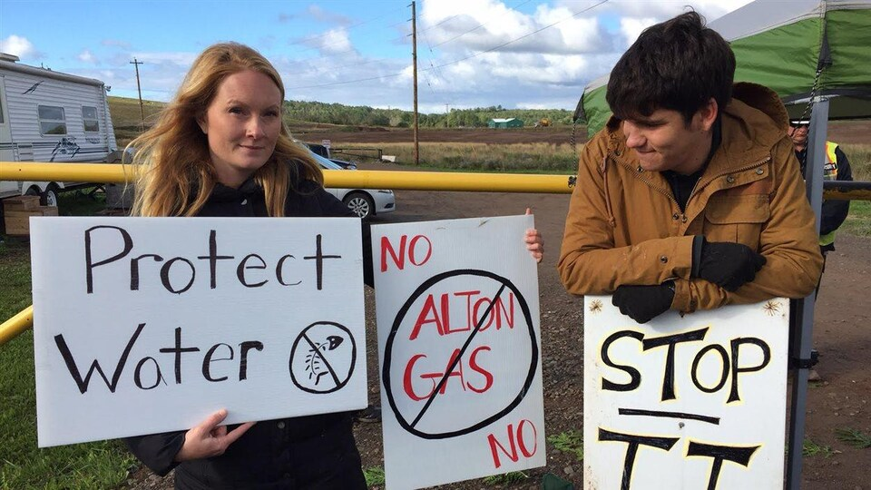 Un homme et une femme qui portent des pancartes sur lesquelles on peut lire «protect water», «no alton gas» ou encore «stop it»