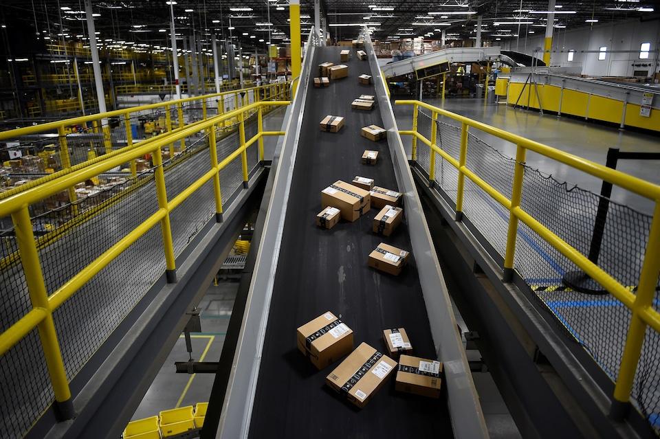 Des boîtes d'Amazon sur un convoyeur.