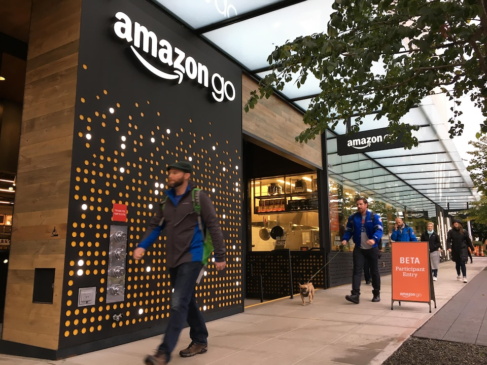 On voit des passants marchant devant le magasin d'Amazon à Seattle.