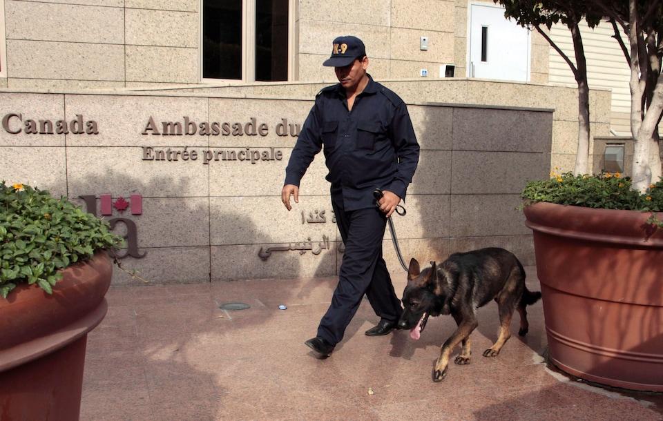 Une photo montre un gardien de sécurité qui marche devant l'ambassade du Canada au Caire, en Égypte.
