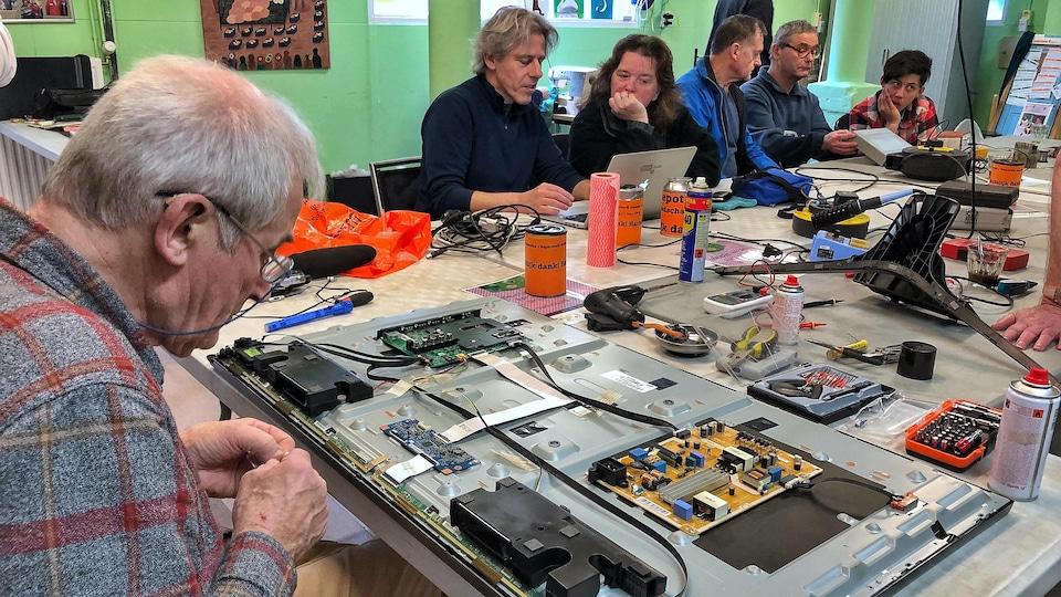 Un bénévole répare un téléviseur au Repair Café De Pijp, à Amsterdam.
