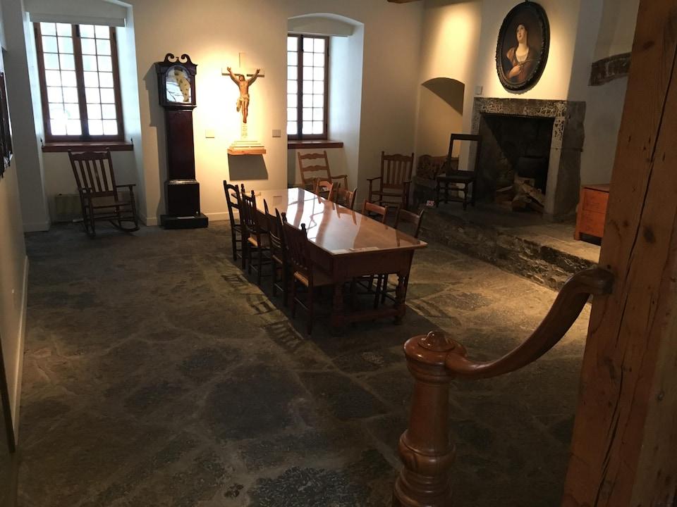 La salle comprends notamment un table, des chaises, un âtre à cheminée et une horloge. Le sol est en pierre et le soleil pénètre dans la salle par deux fenêtres.