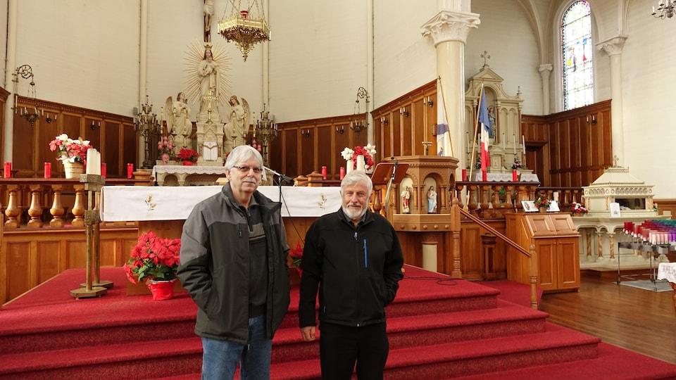 Deux hommes debout devant l'autel de l'église.