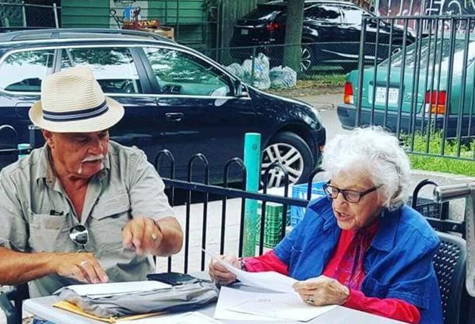 Un homme et une femme âgée assis dehors en été.