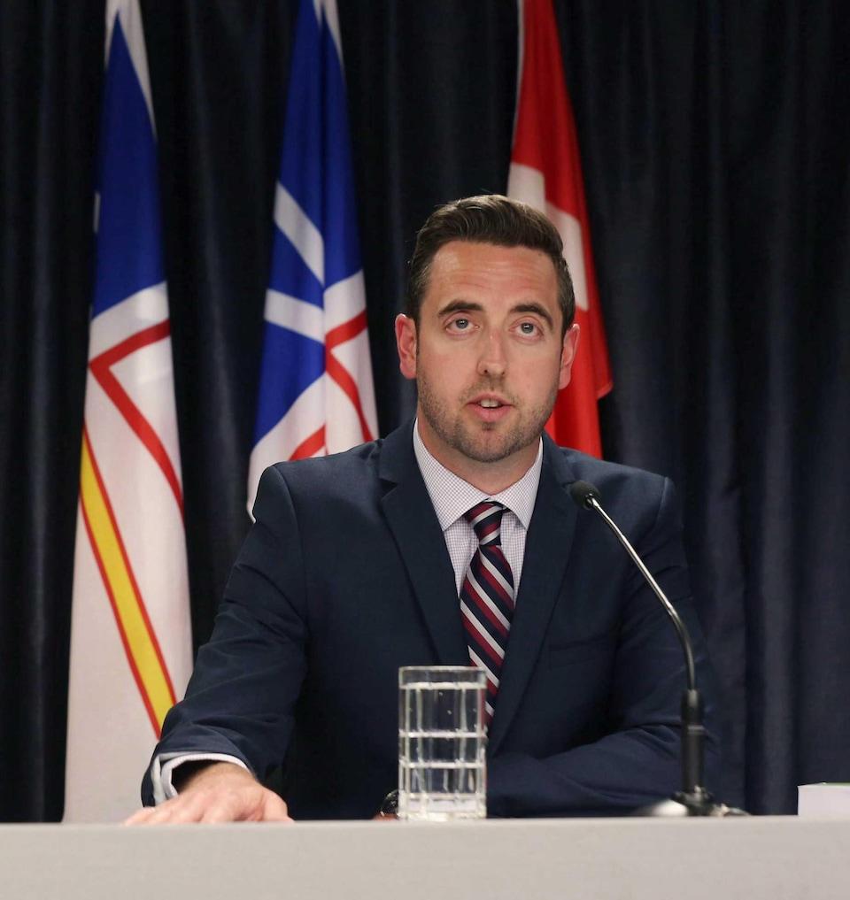 Andrew Parsons assis à une table lors d'une conférence de presse.
