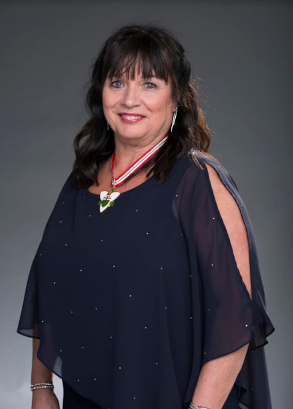 Le portrait d'une femme portant une médaille de l'Ordre de l'Ontario.