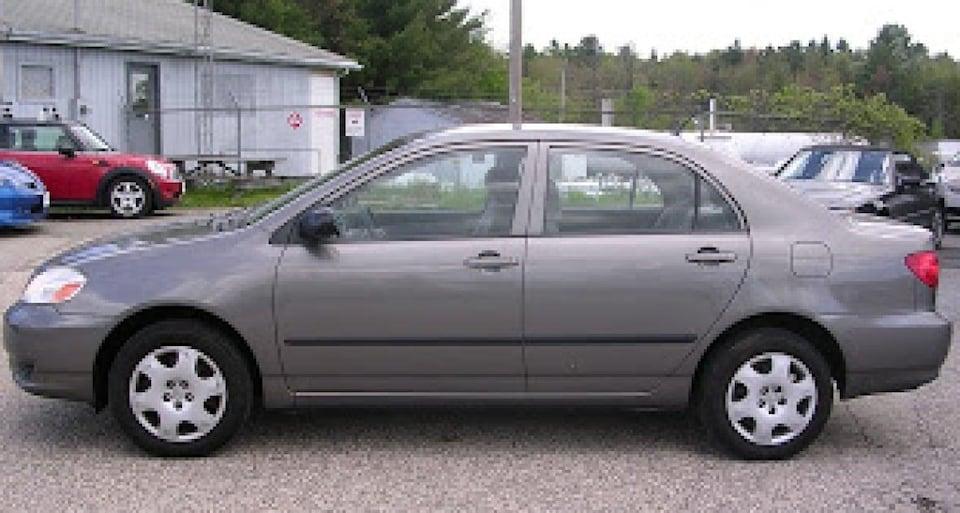 Une voiture à quatre portes de couleur argentée dans un stationnement.