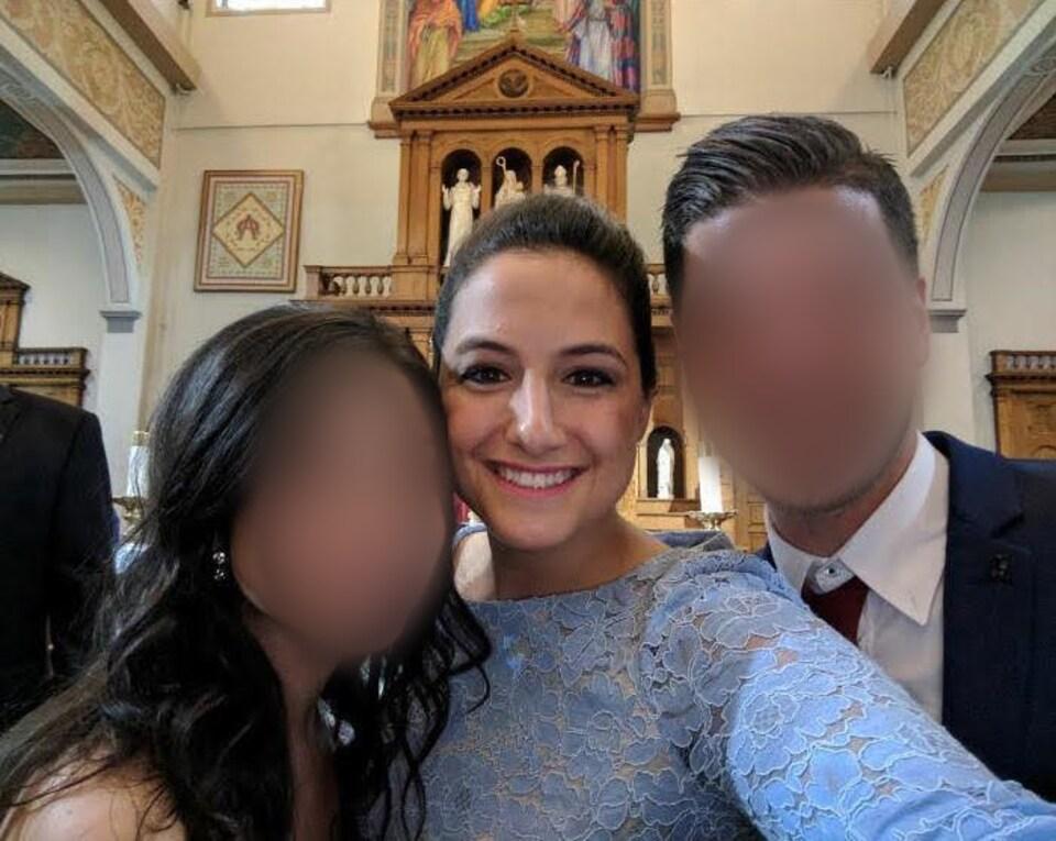 Photo d'une femme en robe bleue entre un homme et une femme.