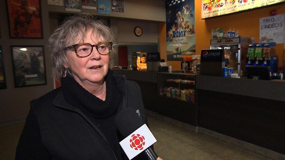 Une femme avec des lunettes parle au micro de Radio-Canada.