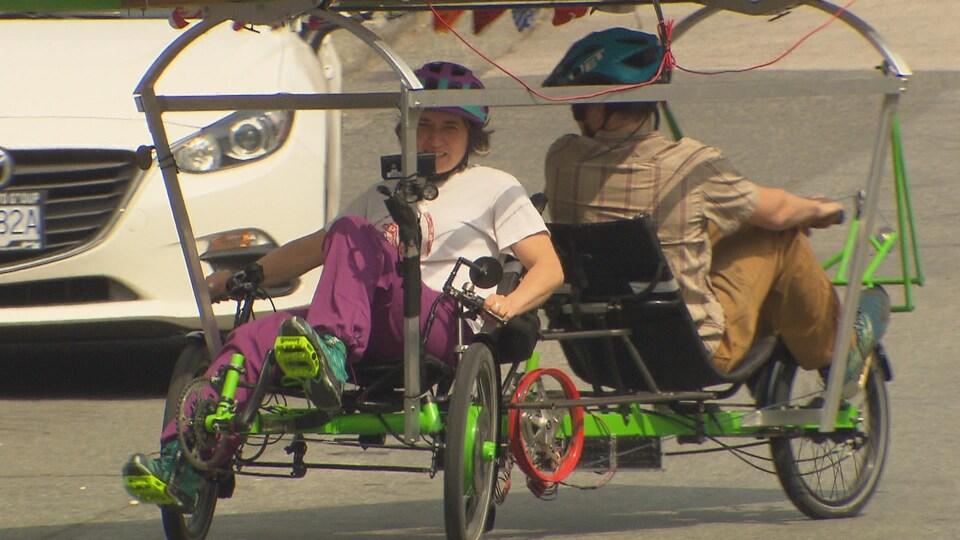 Une femme pédale et un homme rame dans un vélo à énergie solaire.