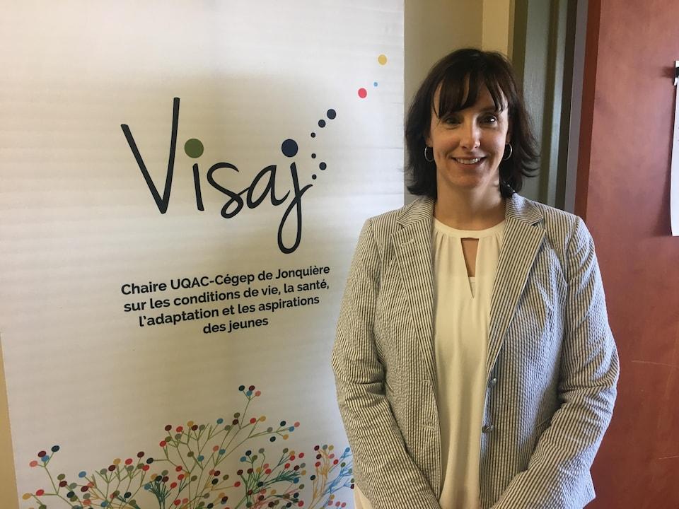 Annie Aimé pose devant une affiche au congrès de l'Acfas.