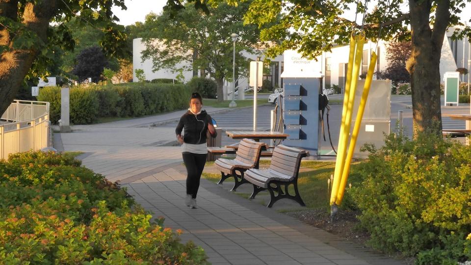 Une femme court sur un trottoir