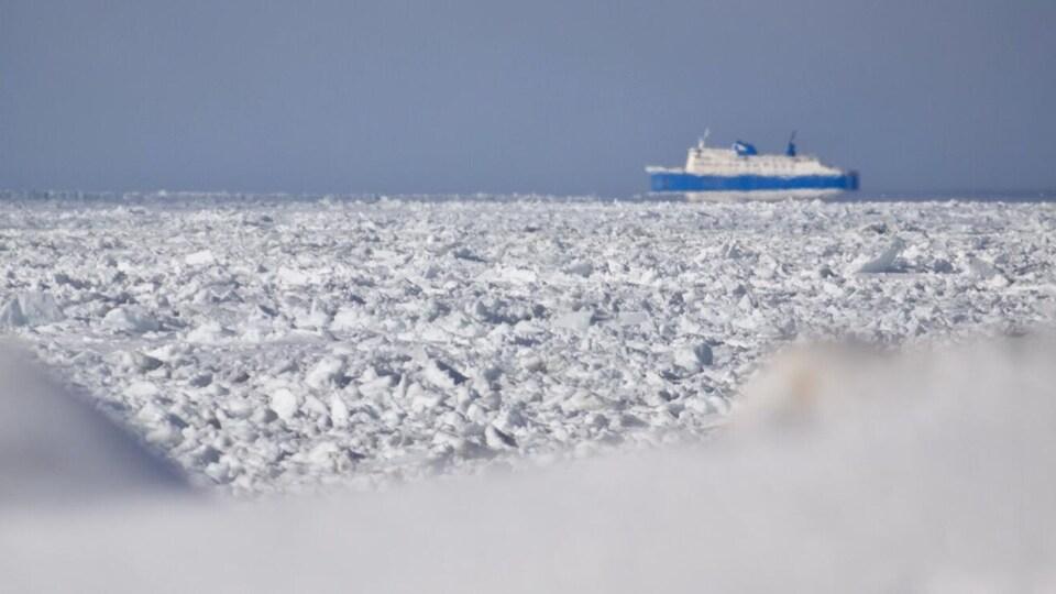 De la glace en avant-plan et le bateau à l'arrière.