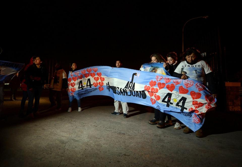 Des gens tiennent une banderole sur laquelle on peut lire ARA San Juan, avec le chiffre 44 entouré de coeurs.