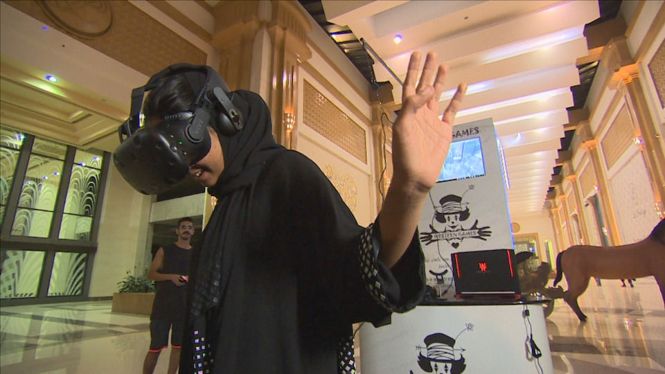 Une jeune femme saoudienne fait l'essai d'un casque de réalité virtuelle.