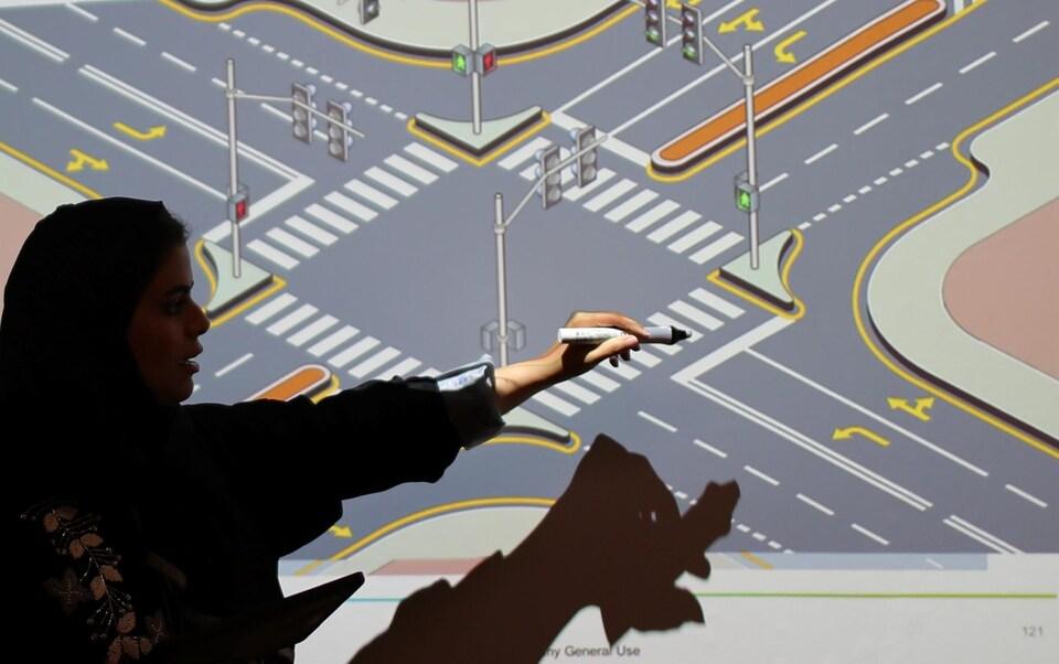 Une instructrice montre les règles de la route sur un écran.