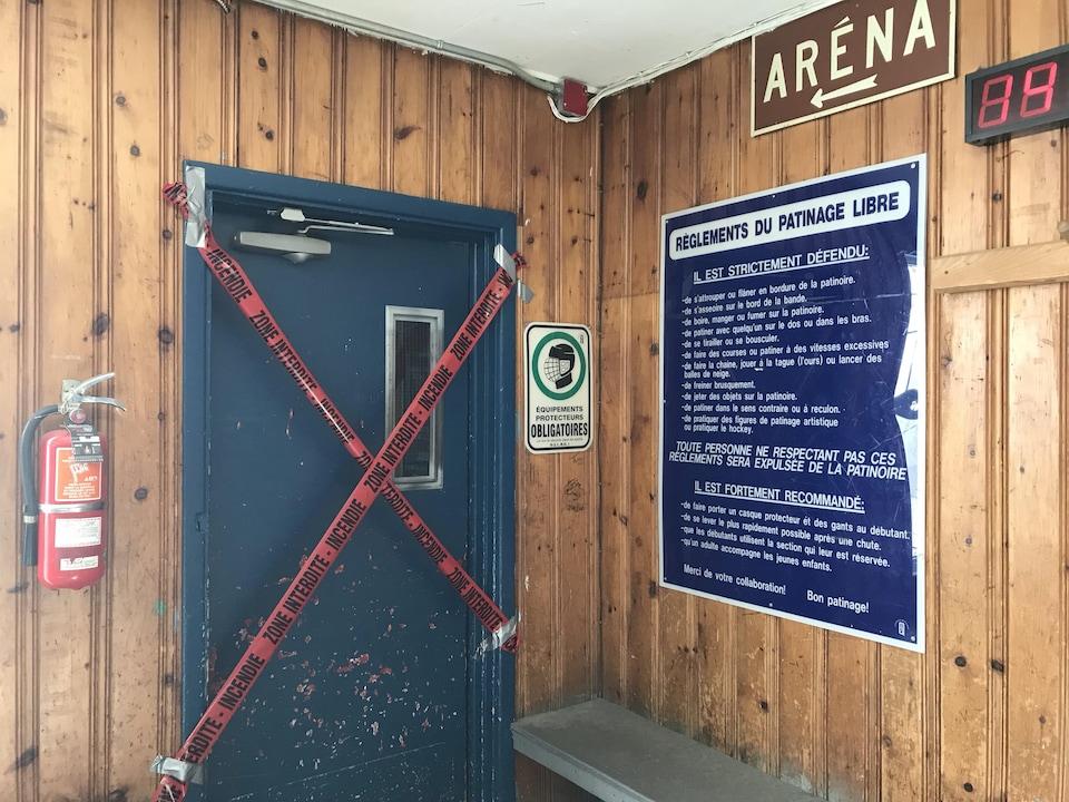 Un ruban rouge positionné en «X» bloque l'accès à une des portes extérieures de l'aréna.