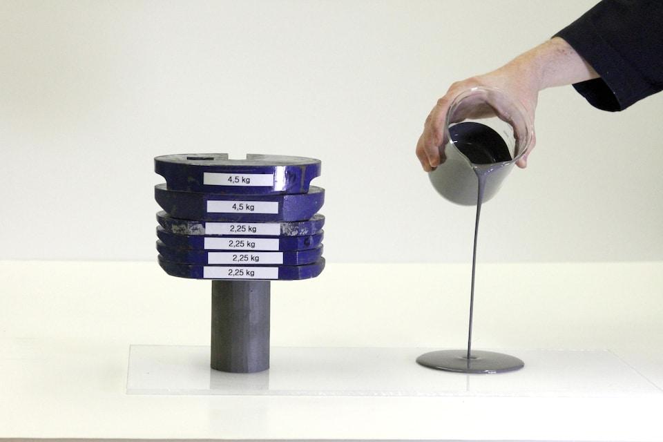 On voit, à gauche, une masse de 18 kilos qui repose sur un échantillon d'argile solide, de forme cylindrique. À droite, quelqu'un verse d'un bécher de l'argile liquide sur la table.