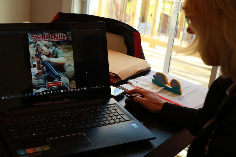 Une photographie illustrant une jeune fille avec un fusil est présentée sur l'ordinateur portable d'Hélène Lescelleur.