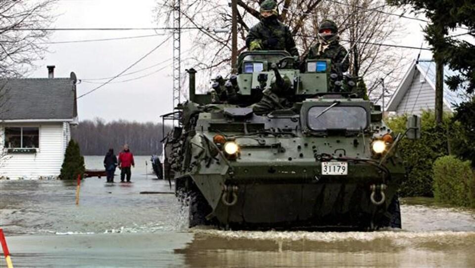 Des militaires canadiens circulent à bord d'un véhicule blindé léger dans un quartier résidentiel inondé de Saint-Jean-sur-Richelieu, en 2011.