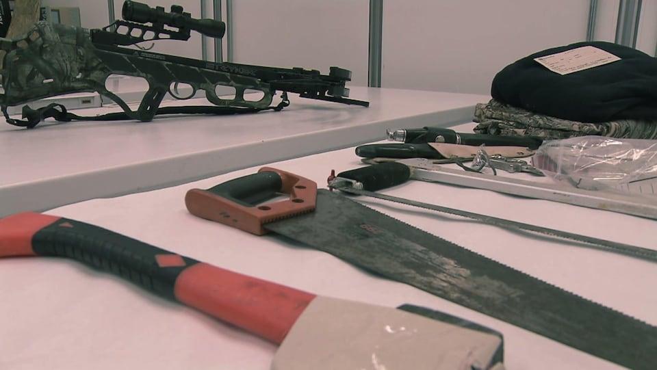 On voit, déposés sur des tables, une hache, des scies, des couteaux, des vêtements de chasse, ainsi qu'une carabine.