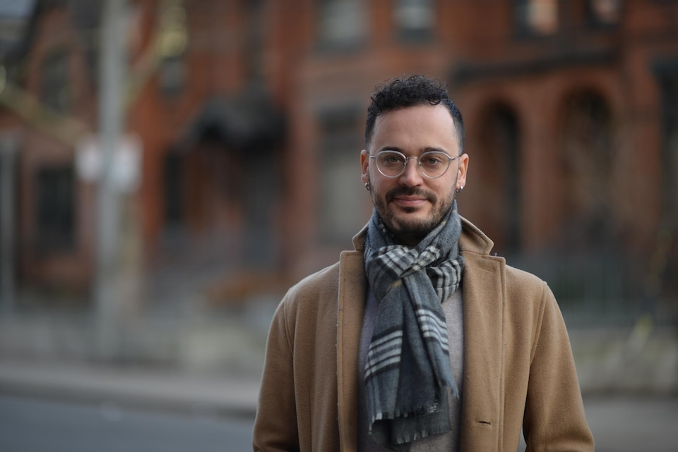 Un homme porte un manteau beige, un foulard noué au cou à carreaux gris et des lunettes rondes de couleur argentée