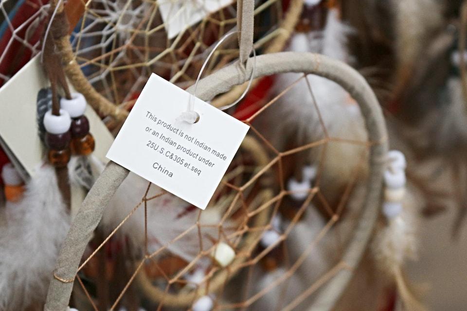 Un capteur de rêves sur laquelle est accrochée une étiquette qui précise que l'objet n'a pas été confectionné par une personne autochtone.