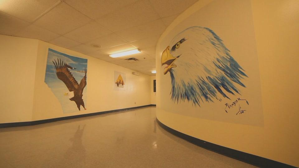 Des peintures autochtones représentant des aigles sur les murs des couloirs de Stan Daniels.