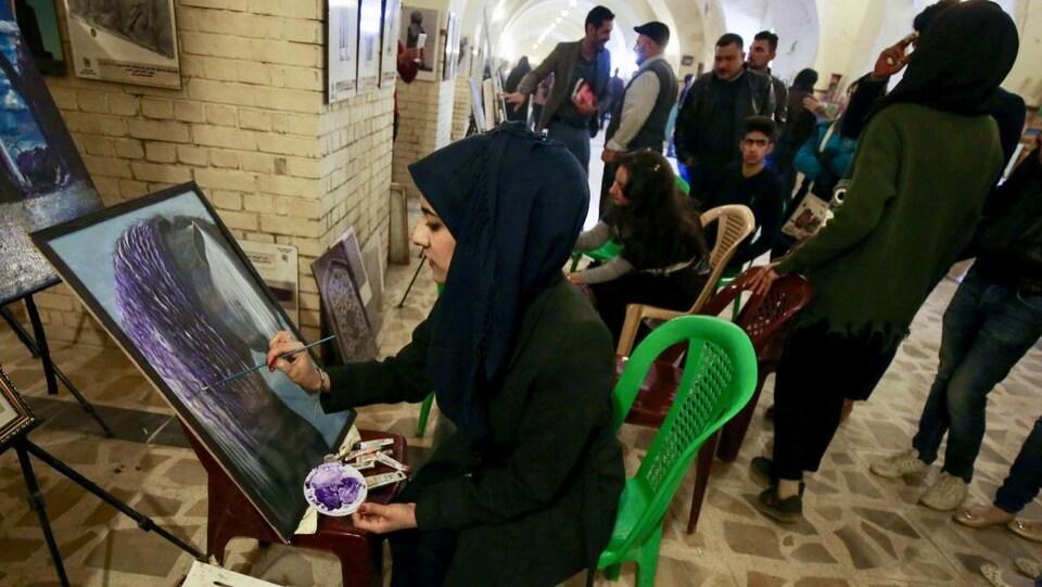 Une image d'une Irakienne qui peint un portrait dans la capitale Bagdad.