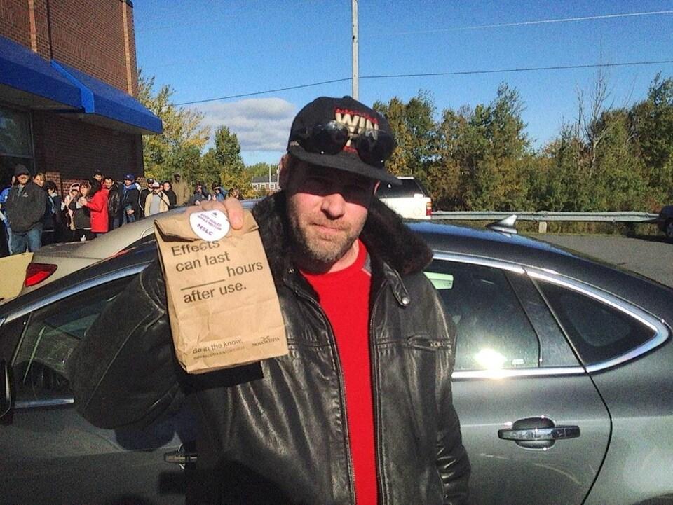 Ashley MacIssac exhibe un sac contenant le cannabis qu'il vient d'acheter.