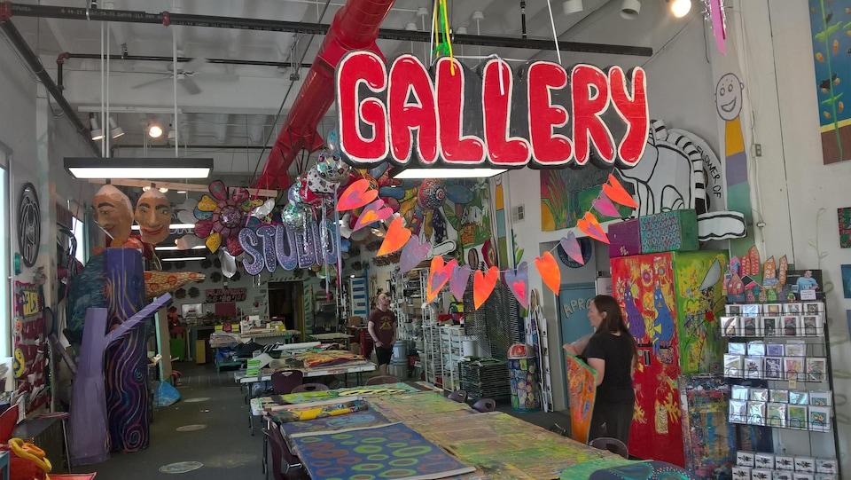 Dans l'atelier Passion Works, de nombreuses oeuvres artistiques sont accrochées au mur ou placées sur de longues tables.