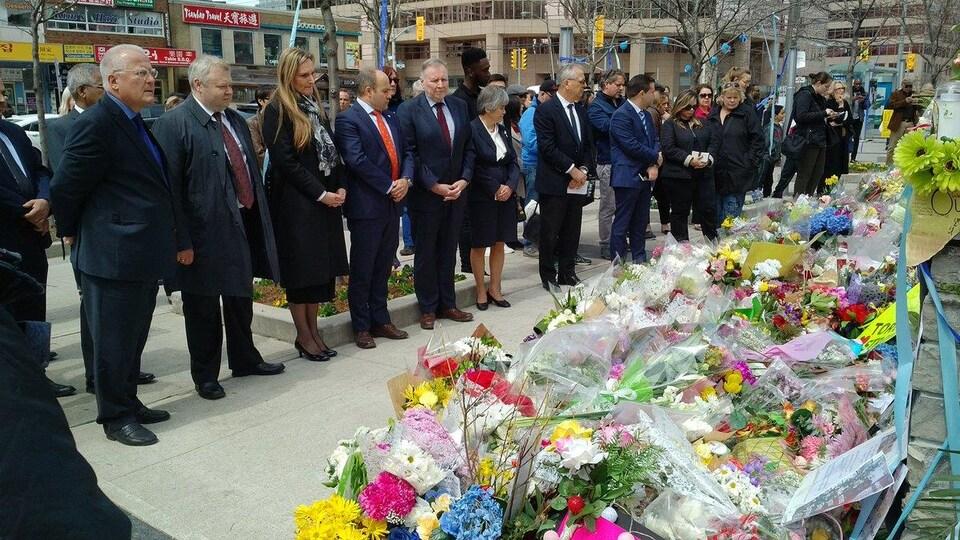 Des diplomates se recueillent devant le mémorial où les gens déposent des fleurs.
