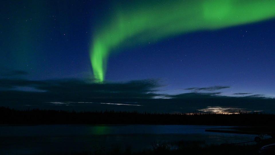 Une aurore boréale traverse le ciel en laissant un reflet sur un lac.